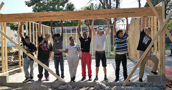 photo of a group of people helping to frame up houses