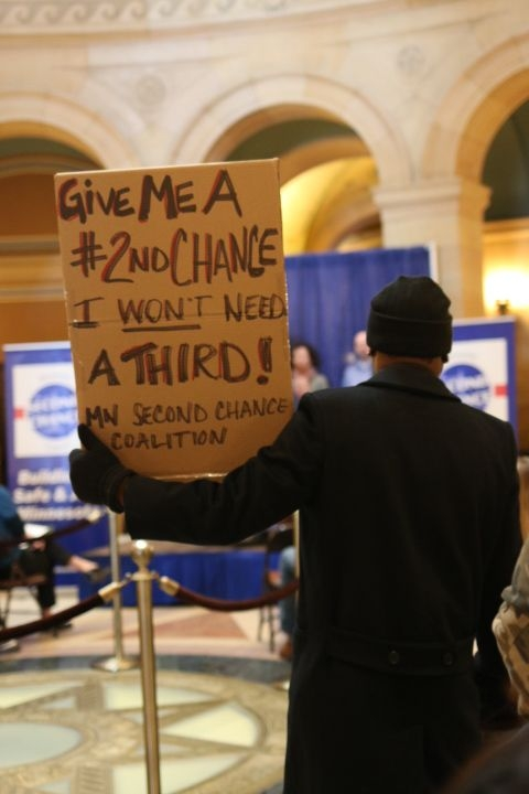 """Second Chance Day attendee holds sign that reads, """"Give me a second chance. I won't need a third."""""""