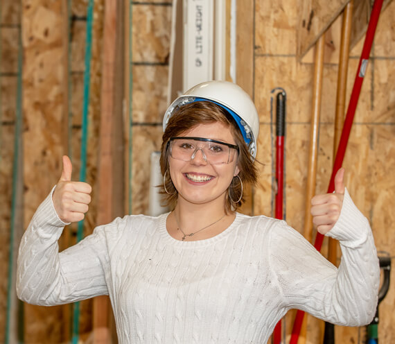 Participant wearing a construciton helmet smiling and giving two thumbs up.