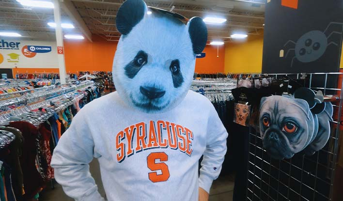 Photo of a person with a panda head mask inside a Goodwill store.