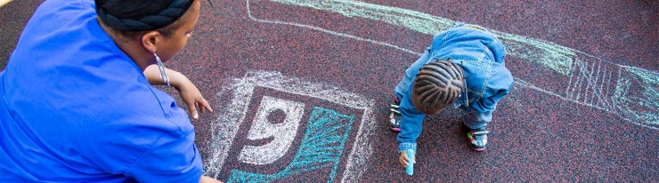 Photo of an adult and a child drawing the Goodwill logo in chalk on asphalt