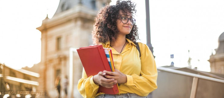 Woman with glasses standing outside holding a binder and some notebooks.