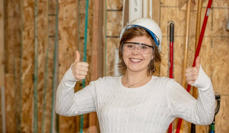 Photo of construction participant smiling with a hard hat on her head.