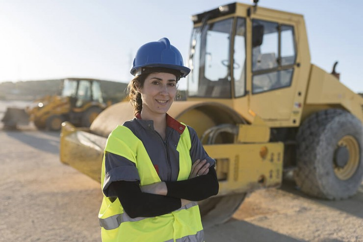Photo of a woman wearing a construction hat and vest standing in front of a bulldozer.