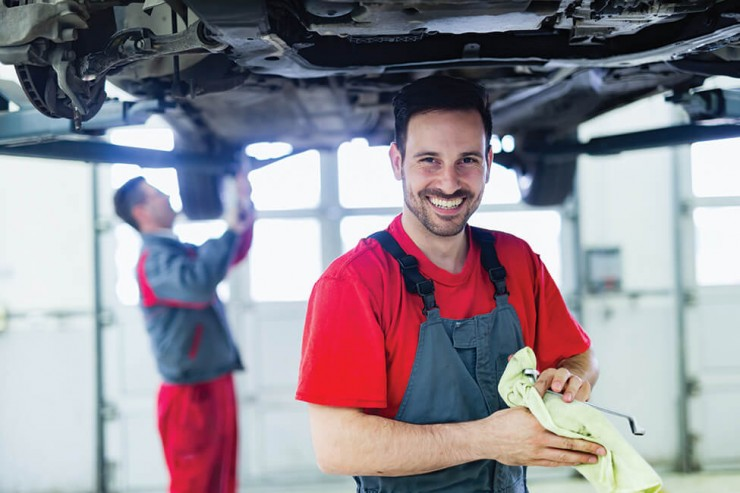 Photo of a man smiling and cleaning his hands in an automotive facility standing under a raised vehicle. of the Automotive