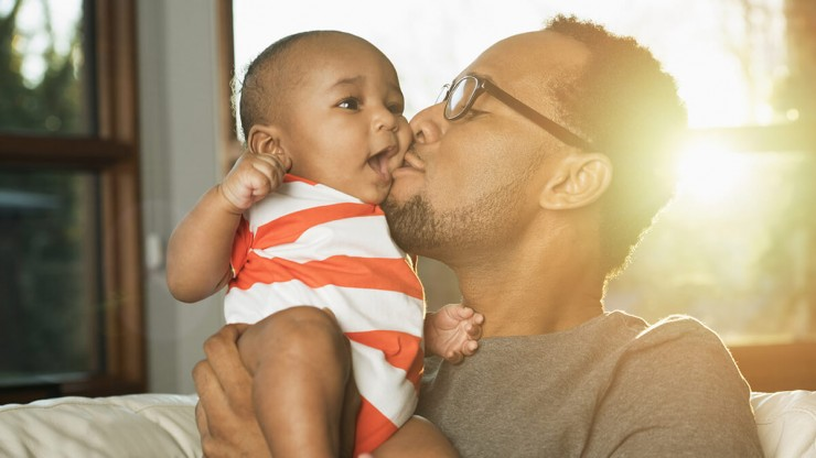 Photo of a father kissing his baby.