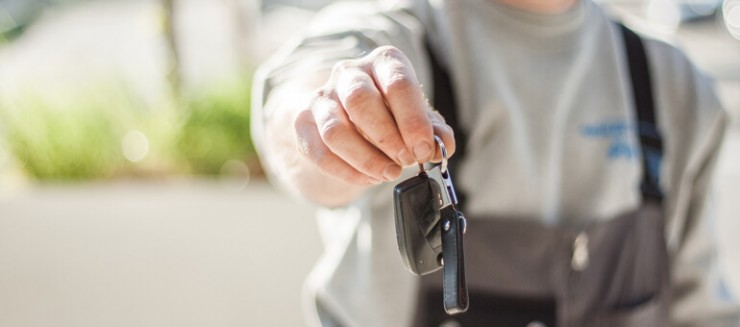 Photo of a person's hand with a car key extending out to hand you the keys.