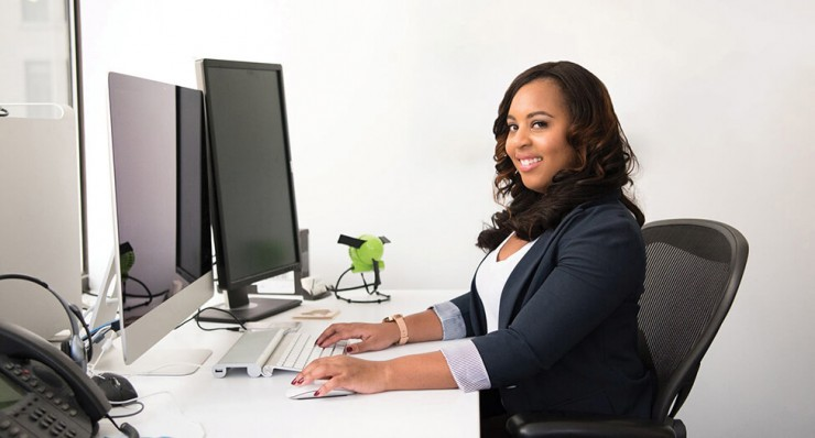 Photo of a women sitting at a desk with her hands on the keyboard