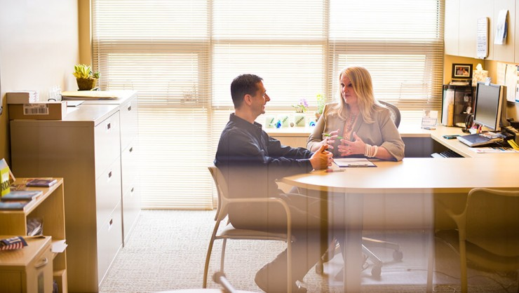 Photo of a man and woman sitting and talking at a desk in an office.